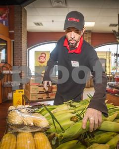 Robert Layman / Staff Photo Tops employee Luie Rivera stocks corn from New England producer Galenski Farms of South Deerfield, MA.