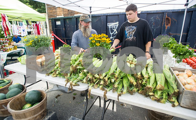 Robert Layman / Staff Photo Paul Flanders, left, and his son Mark stock produce from their family farm at the Castleton Farmers Market Thursday afternoon.