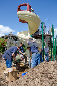 Robert Layman / Staff Photo Over a dozen GE Volunteers work with Pettinelli & Associates, a recreation design firm, to assemble a new playground at Barstow Memorial School in Chittenden Friday afternoon.