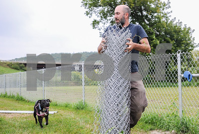 "Robert Layman / Staff Photo While being followed by his dog Roxy, Joe Boudreau carries a roll of chain link fence down to the gates to be installed. ""I didn't realize there wasn't a dog park,"" he said."