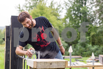 Robert Layman / Staff Photo John Dean, left,  spray paints fencing he's built for a haunted house scene Tuesday, September 5, 2017 in Proctor. Dean originally has organized the Wilson Castle haunted houses but wanted to do it this year at his home  instead.