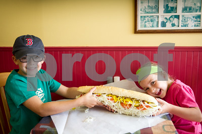 Robert Layman / Staff Photo Brogan Duffy, left, 8, and his sister Rory Veda, 6, hold on tight to a large hot Italian grinder from Gill's Sandwhich Shop Tuesday, September 5, 2017 . Rory and Brogan are the fourth generation to be apart of the family business, which was nominated for the best sandwich in Rutland by Herald readers. See more of the business selected in September 14th's editon of the Herald.