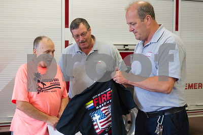 Robert Layman / Staff Photo Henry Fredericks, left, receives a shirt from Bill Lovett, Cheif of the Rutland City Fire Department, and Lt. Robert Miles, center, at the firehouse Wednesday afternoon. The shirt was given to Fredericks after he assisted a resident on Meadow Street contain a fire on August 28, 2017, until the department arrived.