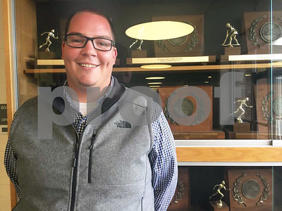 Photo by James Biggam New Harwood Athletic Director Chris Langevin stands in front of the Highlanders' trophy case on Wednesday.