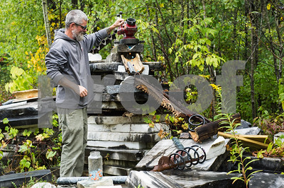 """Robert Layman / Staff Photo Tom Kearns, studio manager at the Carving Studio & Sculpture Center, feeds marbles into Lila Ferber's """"Lost My Marbles,"""" Sculptfest installation which is made of metal, wood and various rock types."""