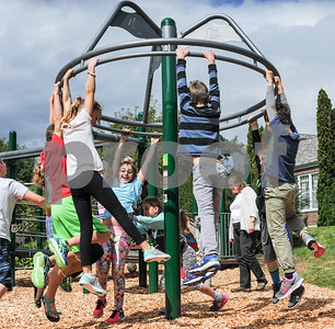 Kids hang on tight as they spin a round an orbiting feature on the new playground at Barstow Memorial School Friday afternoon.