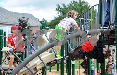 Kids play on a twisted ladder at the new Barstow Memorial School playground Friday afternoon.