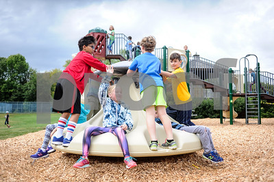 Robert Layman / Staff Photo Fourth and fifth graders ride a new playground feature at the Barstow Memorial School Playground Friday afternoon.