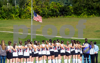NEVER FORGET Robert Layman / Staff Photo  Members of the Rutland High School varsity field hocky team salute a flag flown at half mast before their game against Brattleboro Monday night at Alumni Field.