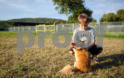 Robert Layman / Staff Photo Carson Meigs, 9, of Rutland, kneels down to pet Dusty a rescue brought in by one of the attendants at the new West Rutland Dog Park Wednesday afternoon. Meigs was at the park Wednesday night with his mother and white labrador named Ira.