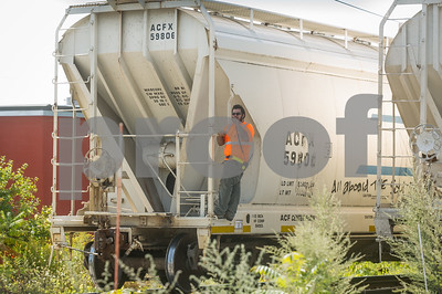 Robert Layman / Staff Photo A rail yard worker rides a car on its way to be switched out Wednesday afternoon.