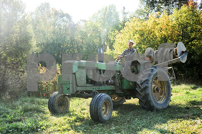 Robert Layman / Staff Photo Timothy Hughes-Muse, co-owner of Laughing Child Farm in Pawlet, drives his tractor away after pulling plastic mulch from a row of sweet potatoes Monday morning.