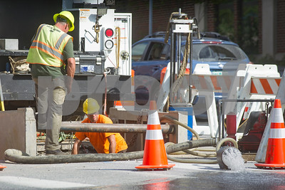 Robert Layman / Staff Photo  Workers from Jack Farrelly Company of Bloomfield, CT, and the Rutland City Department of Public Works drain a water from a water main project onto West Street Tuesday afternoon.