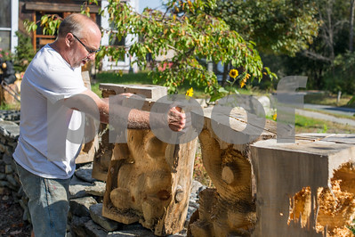 Robert Layman / Staff Photo Barre Pinske arranges some of his rough cut bears outside his carving studio in Chester Monday.