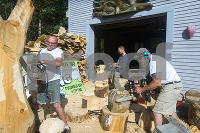 Robert Layman / Staff Photo Despite temperatures climbing near 90 degrees in Chester, a trio of chainsaw carvers carries on. Seen here is Barre Pinske, left, Rich Koonz, center and Tony Falco, right.