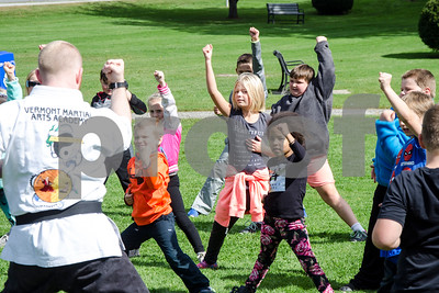 Robert Layman / Staff Photo  Second graders from Northeast Elementary School are guided in a martial arts lesson by instructor DJ Hurlburt, left,  of the Vermont Martial Arts Academy, on the grass at Main Street Park Friday afternoon.