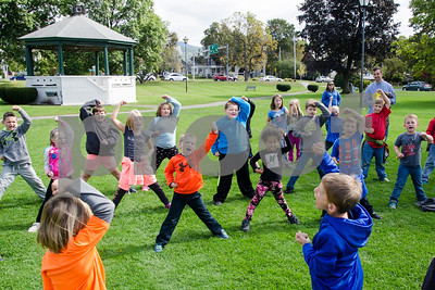 Robert Layman / Staff Photo  Second graders from Northeast Elementary School are guided in a martial arts lesson by instructor DJ Hurlburt, of the Vermont Martial Arts Academy (not pictured), on the grass at Main Street Park Friday afternoon.
