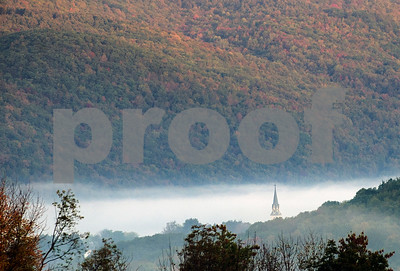 Robert Layman / Staff Photo  As sunlight fades down the mountains surrounding West Rutland, fog covers all the town, save for the steeple from St Bridgets Catholic Church Wednesday morning.