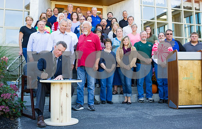 """Robert Layman / Staff Photo  Gov. Phil Scott signs a proclamation making October """"Employee Ownership Month in Vermont"""" on a wooden reel at the Carris Reels headquarters in downtown Proctor Wednesday afternoon, October 4, 2017. Scott's proclamation spoke to the resilancy of the employee-ownership model, stating that it empowers employees financially more than other types. Carris Reels has been employee owned since 1951 and over 2,500 Vermonters work in under this style of ownership."""