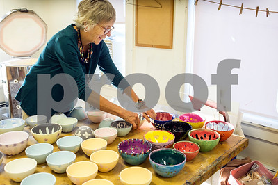 Robert Layman / Staff Photo Penny Coldwell, Mt. Holly Elementary School Art Teacher, arranges students bowls as she does a firing session with her kiln  before classes Wednesday morning, October 4, 2017. Coldwell's classes have been glazing bowls to sell at the upcoming Cider Days Festival in Belmont this upcoming weekend to raise funds for the schools. Parents will be providing cooked items to serve in the bowls while students pedal their pottery.