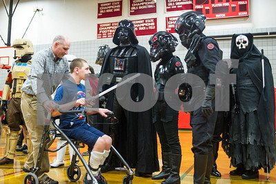 Robert Layman / Staff Photo Ryan Farrington, front left, is wheeled over by his father Sean, far left, to meet Darth Vader, center left, his favorite character for the Star Wars series, and other members of the 501st New England Garrison at his Make A Wish Reveal at Rutland High School gymnasium Tuesday afternoon.