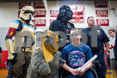 Robert Layman / Staff Photo  Ryan Farrington, 15, bottom right, poses with various Star Wars characters from across the ages -- both in classics and new generation -- as part of his Make A Wish reveal at the Rutland High School gymnasium Tuesday afternoon.