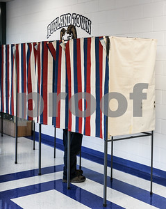 Robert Layman / Staff Photo A person votes at the ballot boxes at Rutland Town School Tuesday evening.