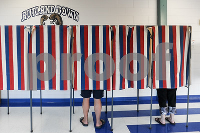 Robert Layman / Staff Photo As the Ram mascott of Rutland Town School peeks over the voting booths, residents vote on Act 49 Tuesday night at the school.