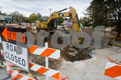 Robert Layman / Staff Photo An excavator loads material back over a large hole on Carver Street in Brandon Wednesday, October 10, 2017. As work crews from Casella Construction were installing pipe Wednesday, October 11, 2017, a watermain was damaged in the process, causing the water supply to be temporarily shut down Wednesday morning to the early afternoon. The accident was attributed to old town schematics that incorrectly mapped where the old main was underneath the road.