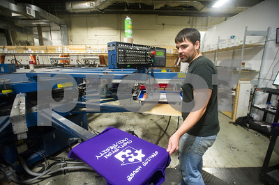 Robert Layman / Staff Photo Luke Harrington, screen printer at Graphic Edge, works the  new 14 color printer in the expanded section of the business' Rutland location Thursday morning October 12, 2017.