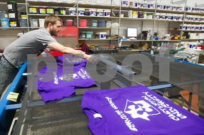 Robert Layman / Staff Photo Cameron Hurst, Screen Printer at Graphic Edge, loads a rack of shirts freshly screened for the Service House of Castleton University in the company's Rutland Location Thursday, October 13, 2017.