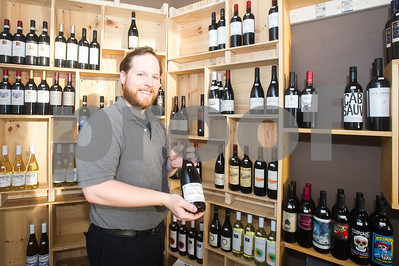 Robert Layman / Staff Photo Adam Atkinson holds up a bottle of red wine inside the new Brix Market in downtown Rutland Wednesday evening. Atkinson is the manager of the shop which operates next to the Brix Wine Bar.