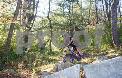 Robert Layman / Staff Photo A mountain biker exits Pine Hill park during a ride Wednesday afternoon.