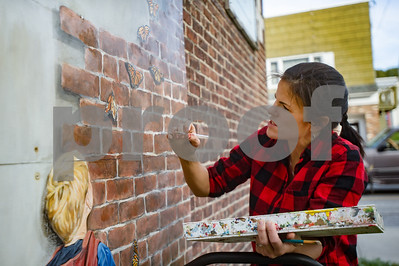 Robert Layman / Staff Photo Local muralist Kathryn Wiegers touches up her 2006 mural on the side of the Rutland Area Food Co-Op Saturday afternoon.
