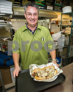Robert Layman / Staff Photo Chris Burque hands off a steak and cheese sub at Olympic Pizza Tuesday night. Burque purchased the business earlier this month.