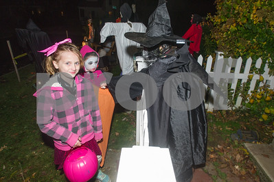 Robert Layman / Staff Photo Madyson, left, and her sister Alyssa Frederick, of Rutland, stop by the Wicked Witch of Newton Street, aka Regeen Wilbur, right, for a handful of candy Halloween, Tuesday, October 31, 2017.