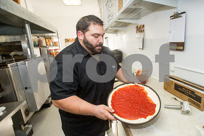 Robert Layman / Staff Photo Mike Esposito, General Manager at  Olympic Pizza, spreads sauce on a pizza Tuesday night. Espositio jumped aboard the business after his long-time friend Chris Burque purhcased the business earlier this month.