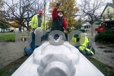 Robert Layman / Staff Photo  Adrian Megrath, center,  president of the Rutland chapter of VVA, points up to crane operator Richard Pietryka, not pictured, as he works on centering the new Vietnam veteran's memorial installation at Maint Street Park Thursday morning. With him are sculptor, Don Ramey, left, who carved the fallen soilder from Danby Imperial Marble, right, Jack Crowther, also a member of the VVA in Rutland. Behind the pair is Danny Hogan, of Fabian Earth Moving, who helped trailer the installation over.