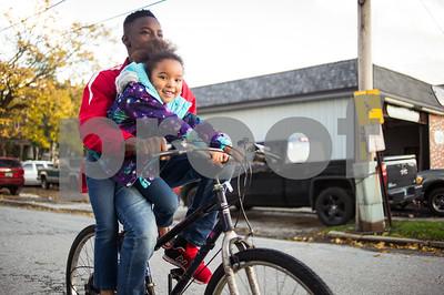 Robert Layman / Staff Photo Taking advantage of the seasonably warm fall, DJ White, 14, left, bikes slowly around Royce Street while his little sister Marianna, 6, rides along Friday night.