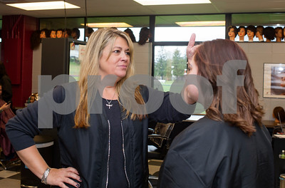 Robert Layman / Staff Photo Stacy Hutchins, left, Cosmetology Instructor, checks the bangs of Emelie Patterson during the classes free day Friday.