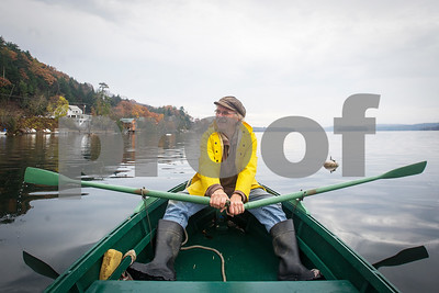 Robert Layman / Staff Photo  Nick Thornblade rows his boat that he built by himself in 1994 out to Mark Joseph's (not pictured) overturned sailboat Thursday, Nov 2 on lake bomoseen. Thornblade was one of the three vessels that aided in the rescue of Joseph's sailboat, which overturned during the windstorm last week. No one was in the boat at the time, and the recovery made for good pictures, see People and Places on Page B8.