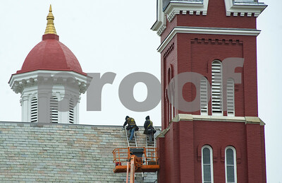 Robert Layman / Staff Photo A pair of roofers work to replace slate tiles high up on the Rutland First Baptist Church Tuesday morning.