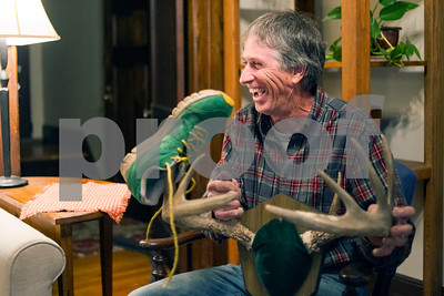 Robert Layman / Staff Photo  Mike Canty smiles as he holds up a set of deer antlers with one of his running shoes hanging from the crowns. Canty, who hunts, is also a long distance runner. The rack was taken from a deer Canty's father hunted at the base of Killington in 1950.