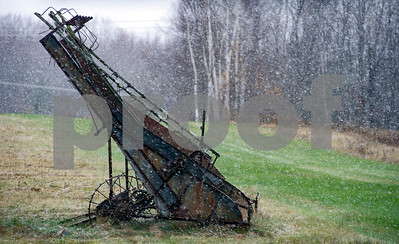 Robert Layman / Staff Photo Snow falls in front of a piece of antique farm equipment in Shrewsbury Tuesday afternoon.