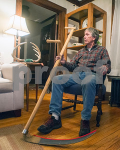 Robert Layman / Staff Photo  Mike Canty talks about sports history with Herald Reporter Tom Haley in Canty's Proctor home Monday night Nov. 6, 2017. He holds a scythe, which in addition to competitive long distance running, he competes with during haying challenges at the Addison County Fair and Field Days.