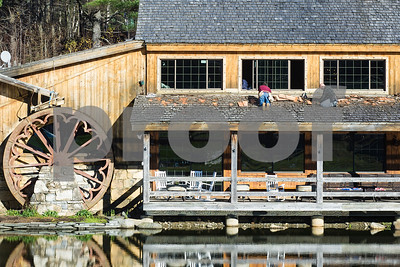 Robert Layman / Staff Photo A pair of roofers repair wooden shingles at The Foundry restaurant in Killington Wednesday afternoon.