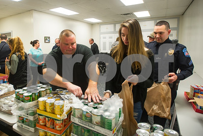 Robert Layman / Staff Photo Sgt. Keith Lorman of the Rutland City Police helps Delaney Kilcullen, center, open a case of string beans as she and Cpl. Jeff Warfle, right, wait to fill it during a food drive at the Project Vision Headquarters Thursday night.
