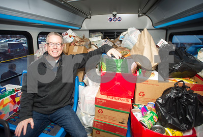 Robert Layman / Staff Photo Tom Donahue, BROC Executive Director, sits happily with a bus during the annual Stuff-A-Bus food drive at the downtown shopping plaza, Friday November 10, 2017. Donahue will be one of the individuals to aggregate all the donations and help share them among the Salvation Army and Vermont Community Cupboard.