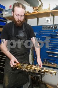 Robert Layman / Staff Photo  Matt Dierickx, who specializes in saxaphones, fixes brass blemishes with metal tools.