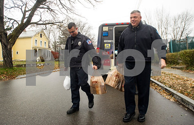Robert Layman / Staff Photo  Officer Emilio Rosario, with the Rutland City Police Department left, and Chief Brian Kilcullen deliver donated food items to members of the community Monday. The food drive was part of an effort of Jackie Lorman through her salon Shear Haven and Sgt. Keith Lorman. Lorman, not pictured, said the police found members of the community through the Salvation Army, local churches, and the community cupboard.